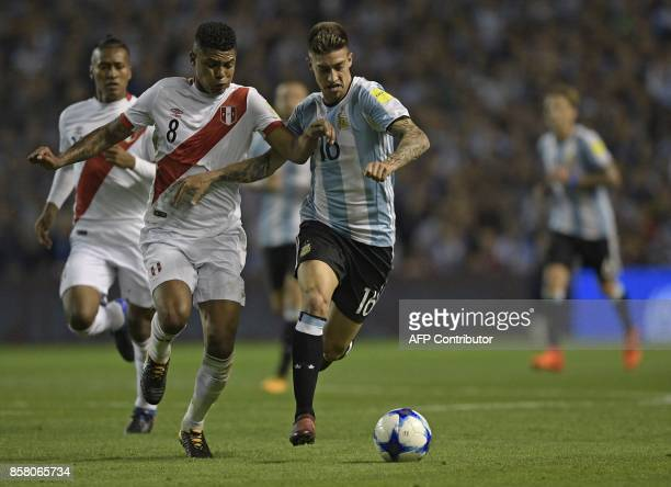 Peru's Wilder Cartagena and Argentina's Emiliano Rigoni vie for the ball during their 2018 World Cup football qualifier match in Buenos Aires on...