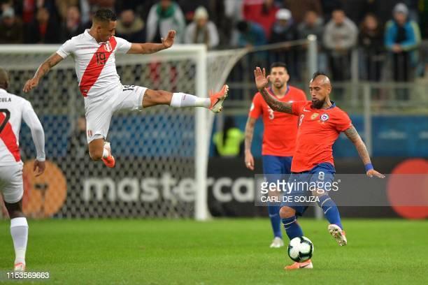 Peru's Yoshimar Yotun jumps to block a strike by Chile's Arturo Vidal during their Copa America football tournament semifinal match at the Gremio...