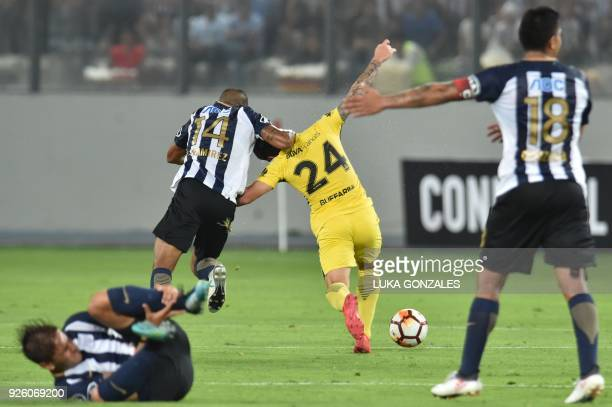 Peruvian Alianza Lima's Luis Ramirez vies for the ball with Argentinian Boca Juniors' Julio Buffarini during their Copa Libertadores football match...