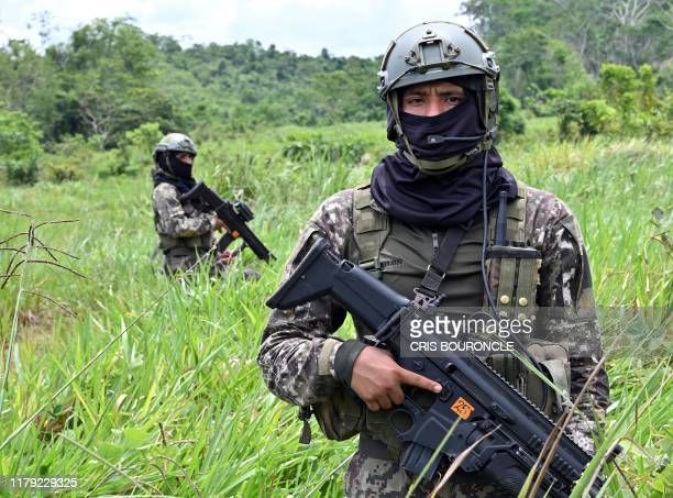 Peruvian Army soldiers stand guard during an operation to blow up a makeshift landing strip used by drug smugglers, in the northeastern Amazon jungle...