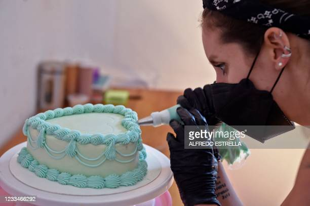Peruvian artist Andrea Ferrero decorates a cake at her bakery in Mexico City on May 11, 2021. - Ferrero and David Ayala-Alfonso are a couple of South...