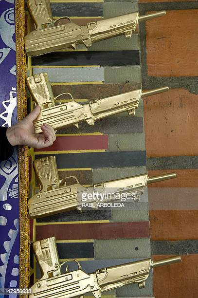 Peruvian artist Cristina Planas Toledo holds a fiberglass gun part of her work Cristo Moreno during the opening of the first mausoleum for victims of...