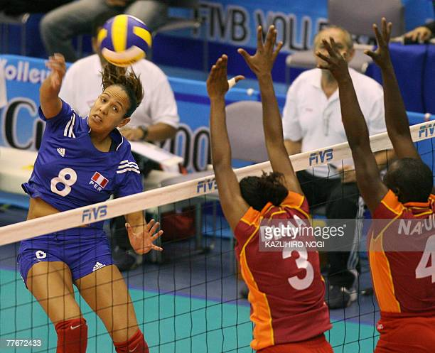 Peruvian attacker Milagros Moy spikes the ball over Kenyan blockers Diana Khisa and Doris Palang'a during a match of the women's World Cup volleyball...