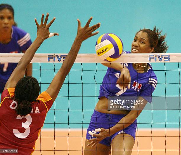 Peruvian attacker Yulissa Zamudio Ore spikes the ball past Kenyan blocker Diana Khisa during a match of the women's World Cup volleyball tournament...