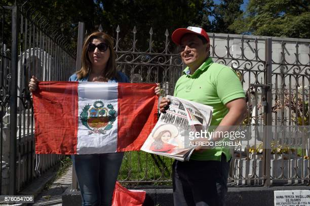 A Peruvian couple pose in front of Mexican singer and actor Pedro Infante's tomb at the Panteon Jardin during the 100th Anniversary of his birth in...