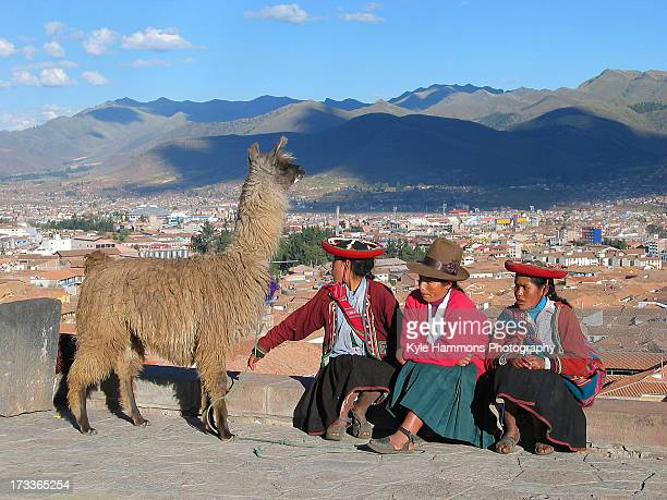 Peruvian family relaxes with their llama on a vista overlooking the city of Cusco Peru