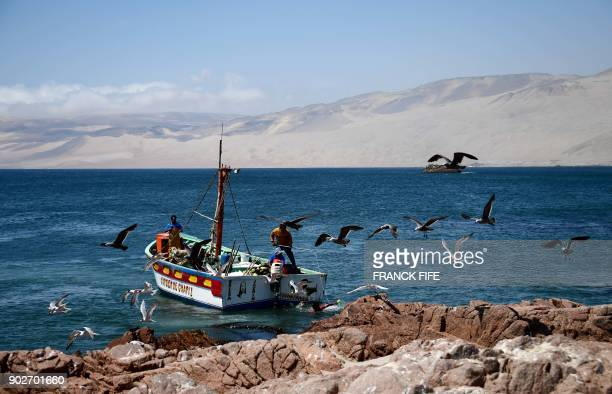 Peruvian fishermen are seen at work during Stage 3 of the Dakar 2018 between Pisco and San Juan de Marcona Peru on January 8 2018 / AFP PHOTO /...