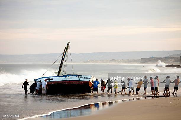 Peruvian fishermen working together to haul boat in for cleaning