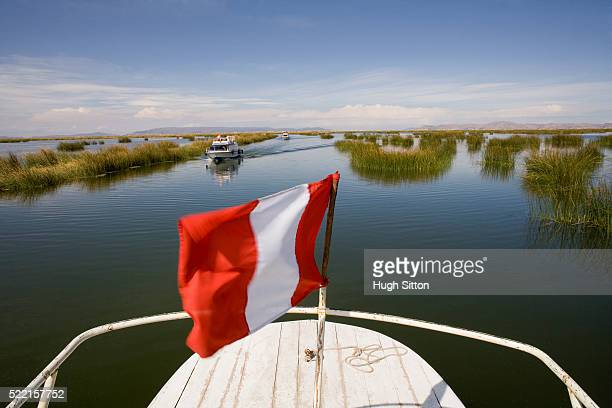 peruvian flag at stern of sightseeing boat on lake titicaca - hugh sitton stock pictures, royalty-free photos & images