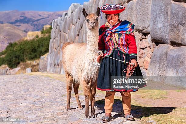 Peruvian girl posing with llama near Cuzco