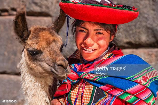 ペルー国民の服を着ている少女の前でポーズを取るラマ近くクスコ - quechua people ストックフォトと画像