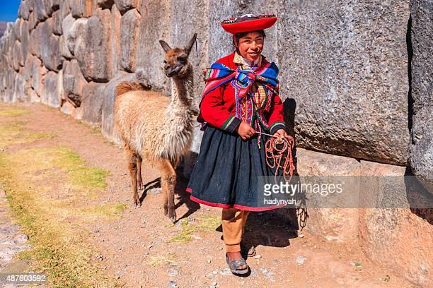 Peruvian girl wearing national clothing posing with llama near Cuzco