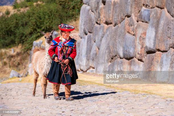 peruvian girl wearing national clothing walking with llama near cuzco - quechua people stock pictures, royalty-free photos & images