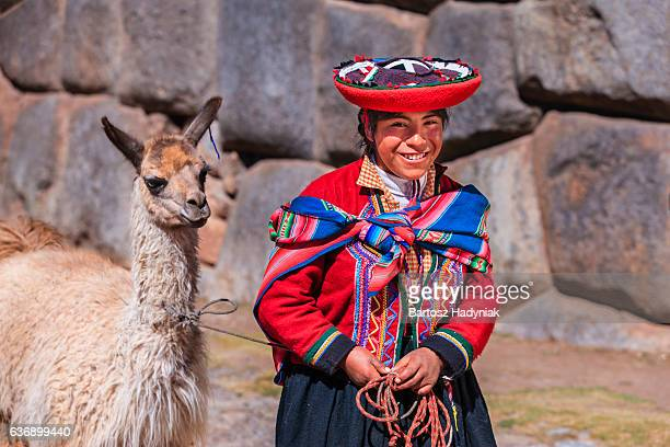 Peruvian girl wearing national clothing walking with llama near Cuzco