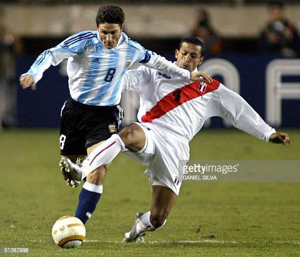 Peruvian Jorge Soto tries to stop Argentina's Javier Zanetti in a match at the Monumental stadium in Lima 04 September 2004 for the FIFA World Cup...