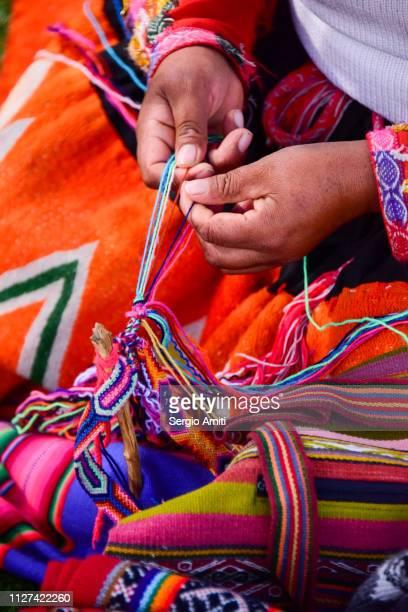 Peruvian lady weaving a friendship bracelet