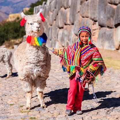 Peruvian little boy wearing national clothing with llama near Cuzco 472079341