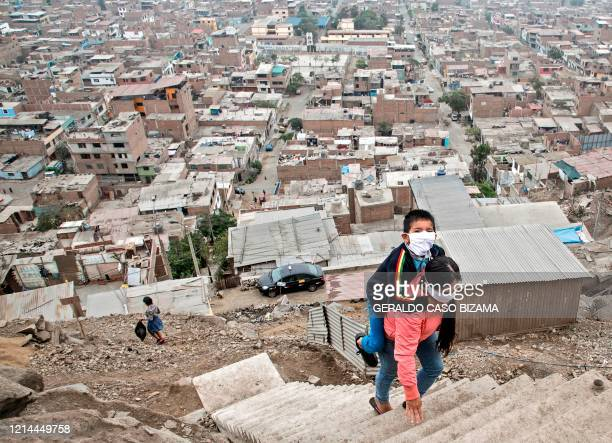 TOPSHOT Peruvian Marlith Mori returns to her home on the heights of the Vista Alegre shantytown of the Comas district in the outskirts of Lima...