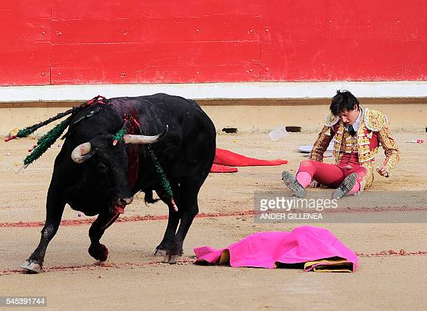 Peruvian matador Andres Roca Rey sits on the ground after being gored by a Fuente Ymbro's bull during the first corrida of the San Fermin Festival in...