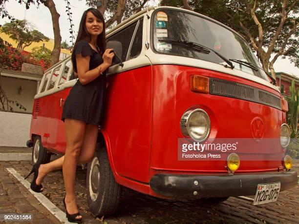 Peruvian model Olenka Guerovich posing on a red and white Volkswagen T2 14 windows Brazilian Kombi