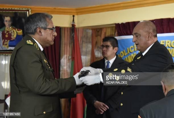 Peruvian National Police commander Richard Douglas Zubiate hands over a seized rifle to his Bolivian counterpart Alfonso Mendoza in the border city...