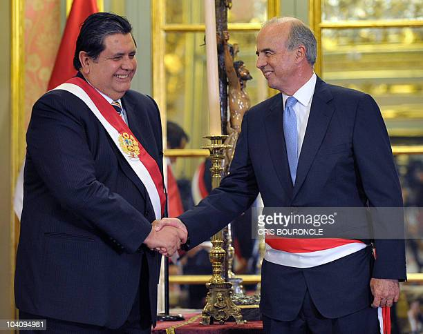 Peruvian new Minister of Economy and Finance independent Ismael Benavides shakes hands with Peruvian President Alan Garcia during a ceremony at the...