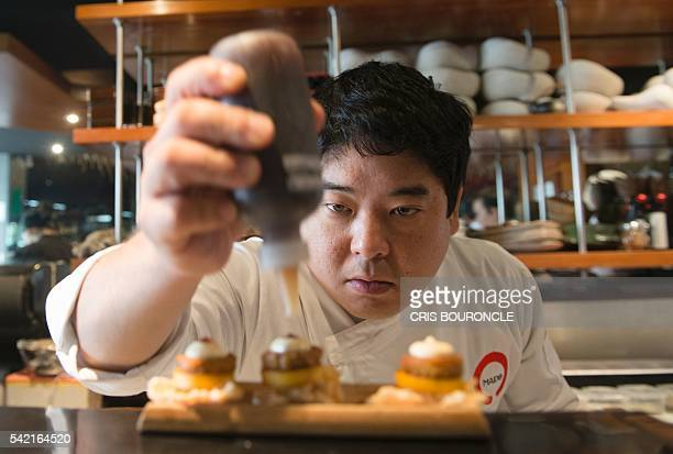 Peruvian Nikkei chef Mitsuharu Tsumura known as Misho places the final touches on a dish of his creation at the Maido highcuisine restaurant in Lima...