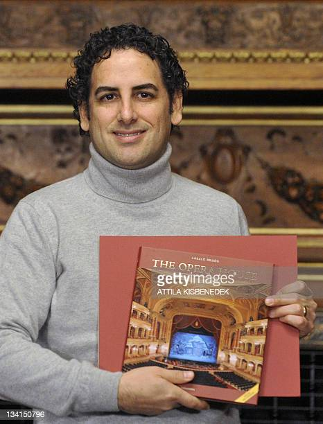 Peruvian operatic tenor Juan Diego Florez poses with a book of the Budapest Opera in the Bertalan Szekely hall of the National State Oper on November...
