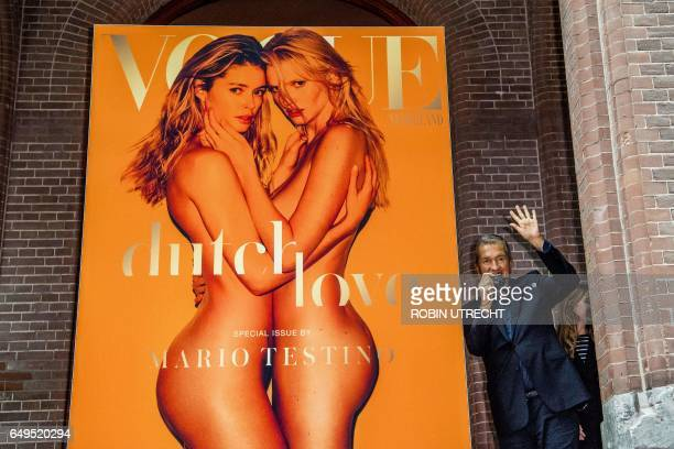 Peruvian photographer Mario Testino waves at the presentation of a special anniversary edition of Vogue Netherlands in Amsterdam on March 8 next to a...