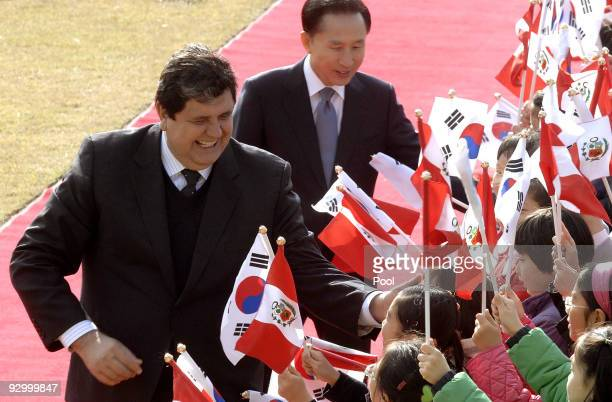 Peruvian President Alan Garcia and South Korean President Lee MyungBak greet South Korean children during a welcoming ceremony held at the...