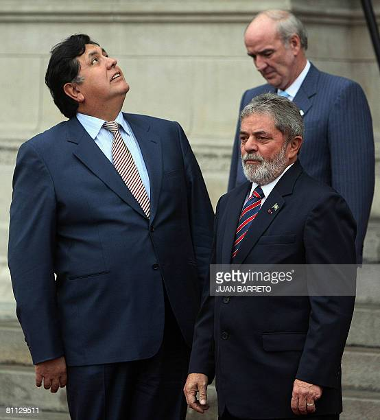 Peruvian President Alan Garcia looks up into the sky next to Brazilian President Luiz Inacio Lula Da Silva as Peruvian Foreign Minister Jose Garcia...