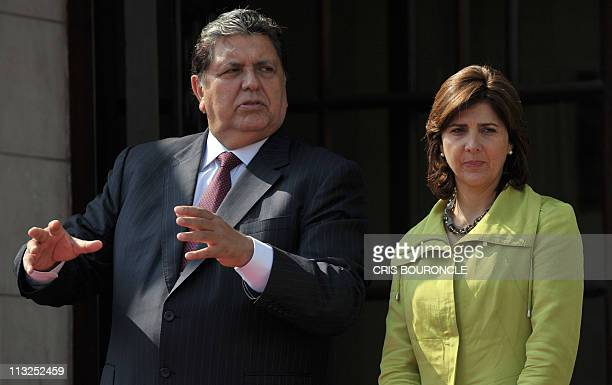 Peruvian President Alan Garcia talks with Colombian Foreign Minister Maria Angela Holgin as they wait for the arrival of Colombian President Juan...