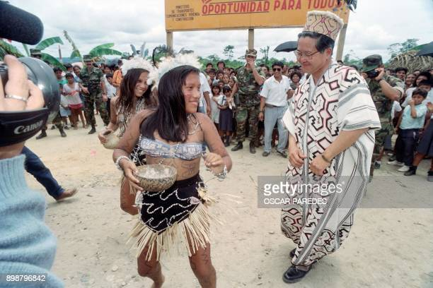 Peruvian President Alberto Fujimori dances in a traditional Ashaninka Indian costume with two Ashaninka women during a visit in the Atalaya region...