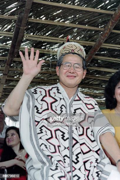 Peruvian President Alberto Fujimori greets people as he wears a traditional Ashaninka Indian costume during a visit in the Atalaya region 700 kms...