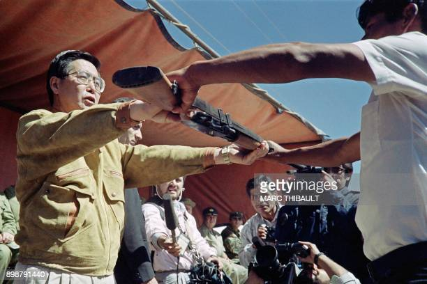 Peruvian President Alberto Fujimori hands a weapon to a peasant in Huancayo on June 23 1991 Fujimori travelled deep into the Andes to distribute...