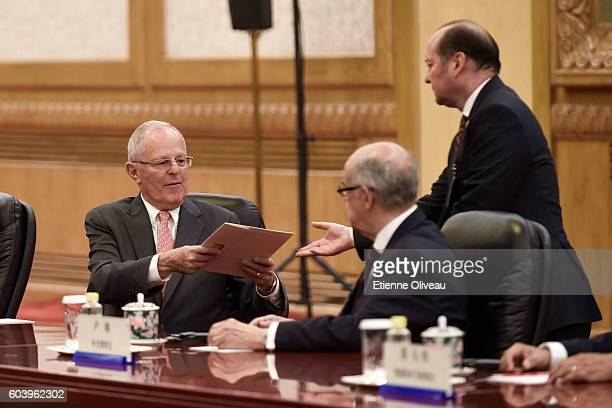 Peruvian President Pedro Pablo Kuczynski handles a file to an official during a meeting with Chinese President Xi Jinping at the Great Hall of the...