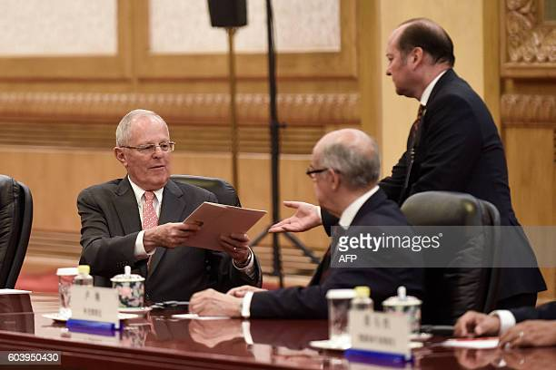 Peruvian President Pedro Pablo Kuczynski hands a file to an official during a meeting with Chinese President Xi Jinping at the Great Hall of the...