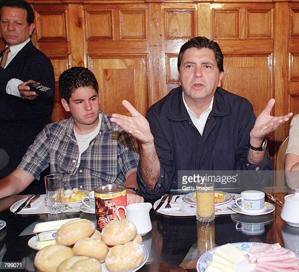 Peruvian presidential candidate Alan Garcia right talks with the press while having breakfast with his son left and his wife April 8 2001 in Lima...
