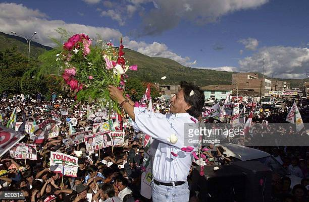 Peruvian presidential candidate Alejandro Toledo shows of flowers given to him by supporters March 30 2001 during a campaign rally in Huanta Peru...