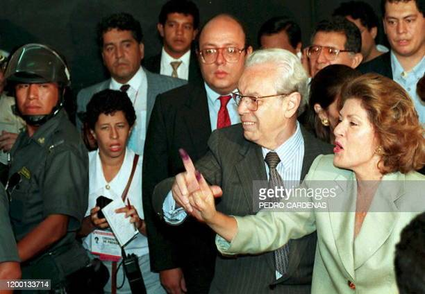 Peruvian presidential candidate Javier Perez de Cuellar and his wife Marcela Temple flash their inked fingers to reporters 09 April 1995 shortly...