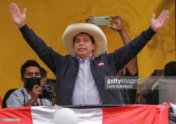 Peruvian presidential candidate Pedro Castillo gestures at supporters from a balcony of his party's headquarters in Lima on June 7 after taking a...