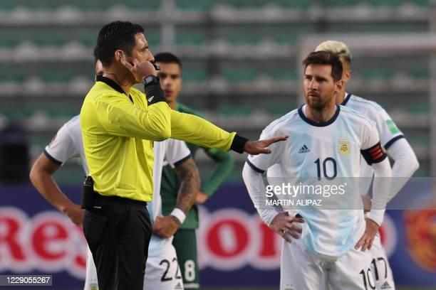 Peruvian referee Diego Haro checks a situation with the VAR as Argentina's Lionel Messi waits during the 2022 FIFA World Cup South American qualifier...