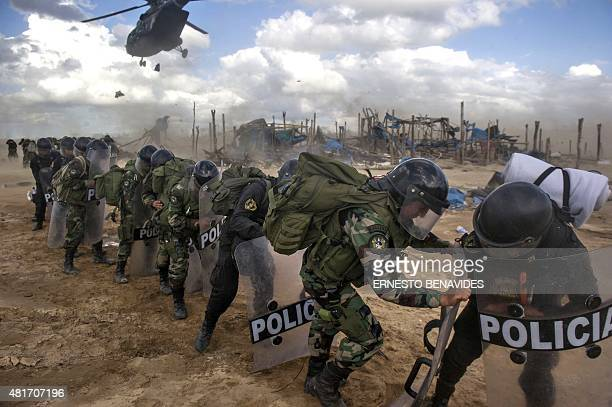 Peruvian riot police await for their transport helicopters to land to pick them up by at the end of an interdiction operation in the illegal gold...