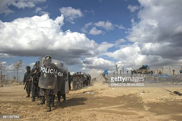 Peruvian riot police stand by at the end of an interdiction operation in the illegal gold mining area of La Pampa in Madre de Dios southern Peruvian...