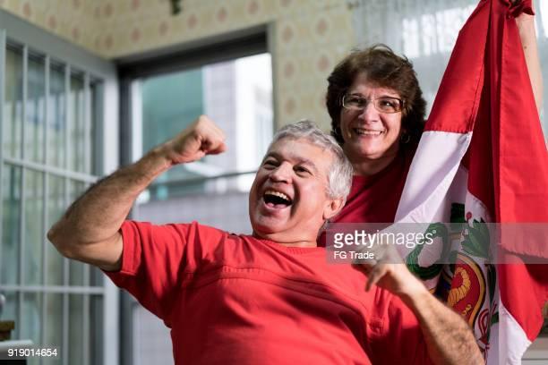 fan peruana pareja senior viendo partido de fútbol en casa - perú fotografías e imágenes de stock