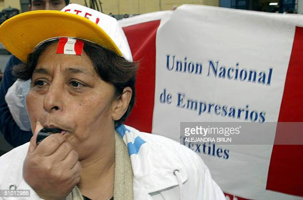 Peruvian small textile businesswoman blows a whistle as she participates 30 June 2004 in Lima in a protest rally in front of the Congress against the...