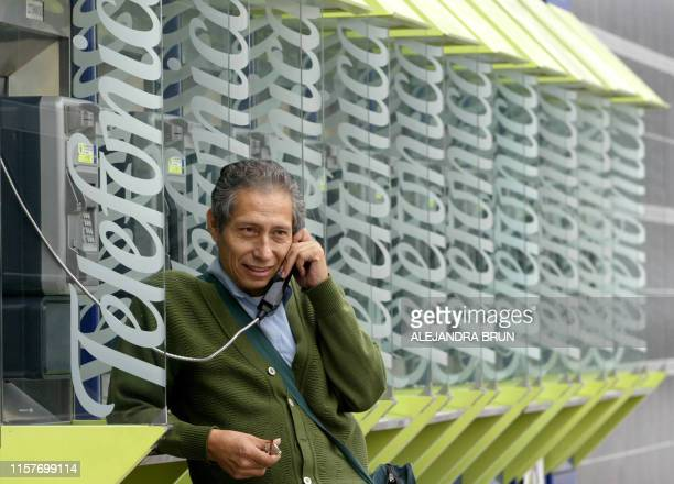 Peruvian speaks from a public telephone supplied by the Spanish transnational Telefonica, in Lima on June 10, 2004. The government of Peru decided...