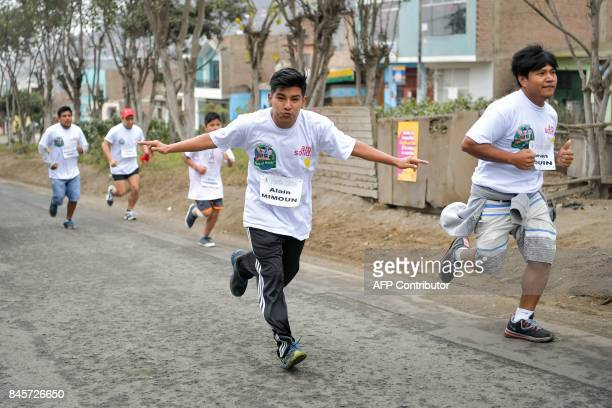 Peruvian teenagers take part in a race organized during a visit of the Paris 2024 Olympic bid to a humanitarian project at the Collique shantytown in...