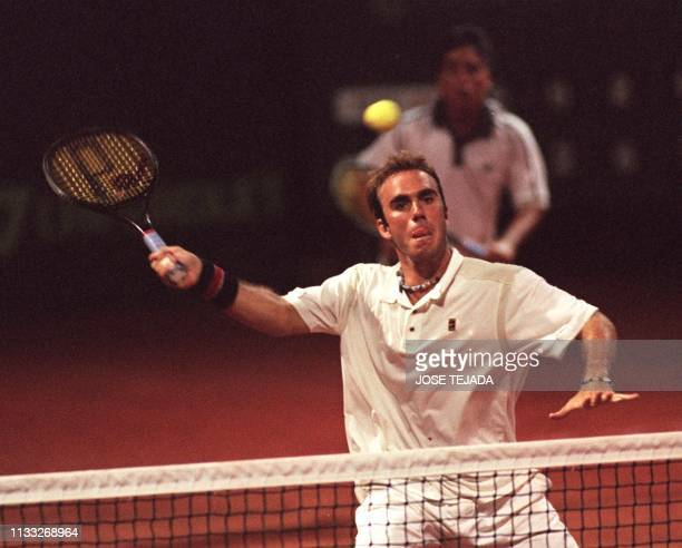 Peruvian tennis player Luis Horna hits a low ball under the watch of his partner Tupi Venero during a Davis Cup match in Lima 07 April 2000 El...