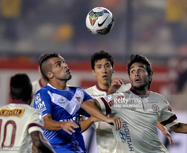 Peruvian Universitario's players David Gomez and Dalton Moreyra surround Argentinian Velez's player Hector Canteros during their Libertadores Cup...